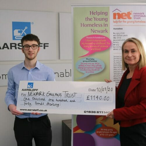 Aarsleff's Marketing Assistant Harrison presenting Newark Emmaus Trust CEO Nikki Burley with a cheque.